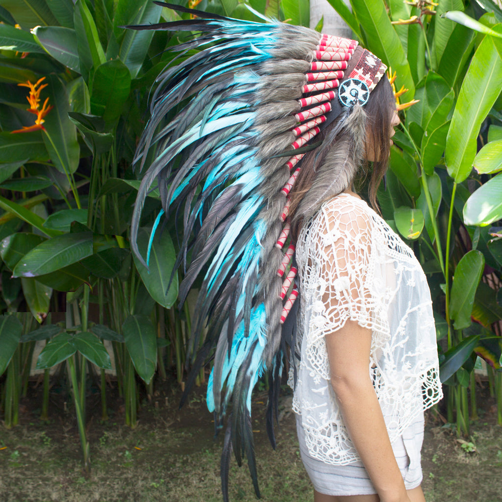 photo of a girl wearing long turquoise indian headdress with leather, beads, and turquoise rooster feathers, for men, for women, or for children, available for purchase from the sounding iron with shipping from the united states
