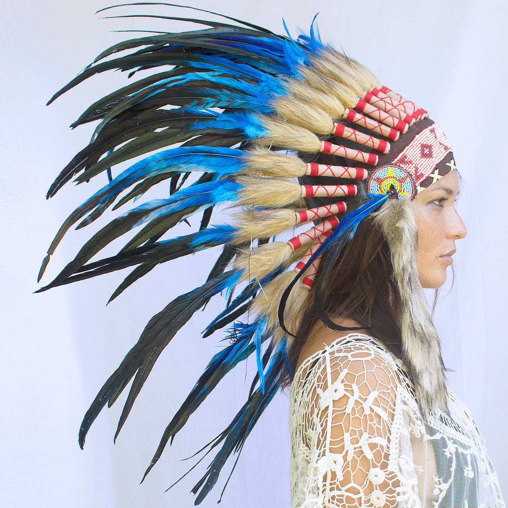 photo of a girl wearing a short blue indian headdress with beads and blue rooster feathers, for men or for women or for children, available for purchase from the sounding iron with shipping from the united states