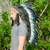 photo of a man wearing a long blue headdress with double feathers