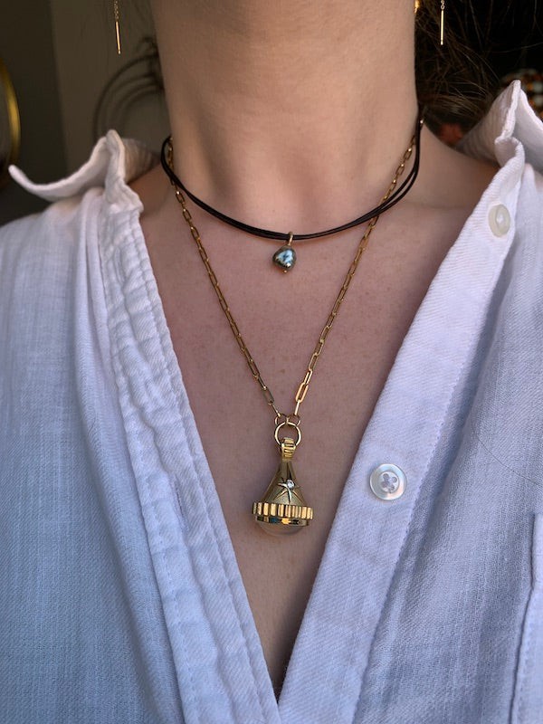 Petite Baleine Keshi Tahitian Pearl and Leather Necklace layered with Pamela Zamore 18k Gold Star Fob with Moonstone Necklace on a woman's neck