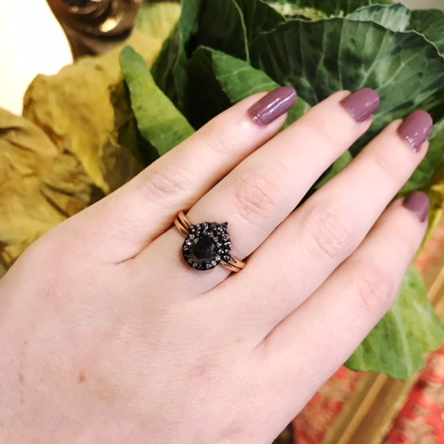 An engagement ring and band set of 14k rose gold with a rose cut black diamond and a rhodium plated white diamond halo on a woman's ring finger