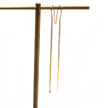 14k yellow gold thin herringbone chain earrings hanging from an earring stand