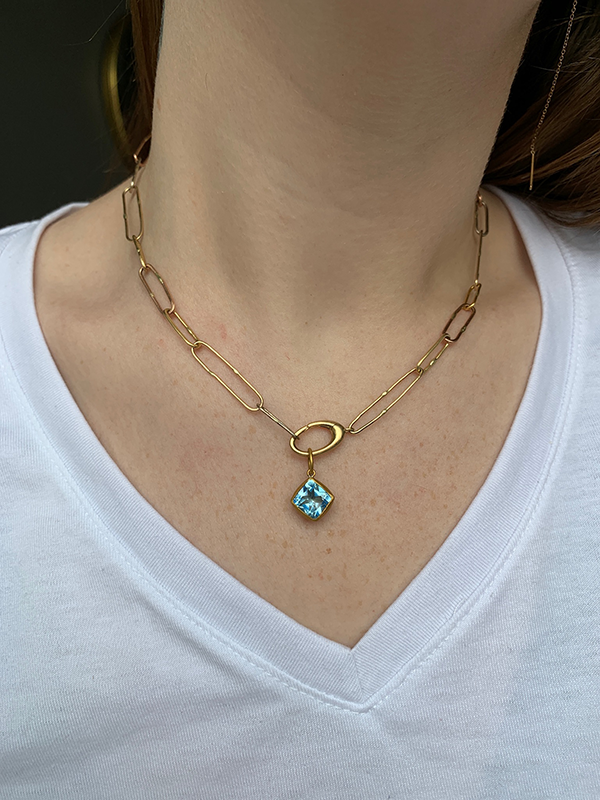 24k Gold + Blue Topaz Charm modeled on a Variance Objects solid gold link chain necklace on a woman's neck