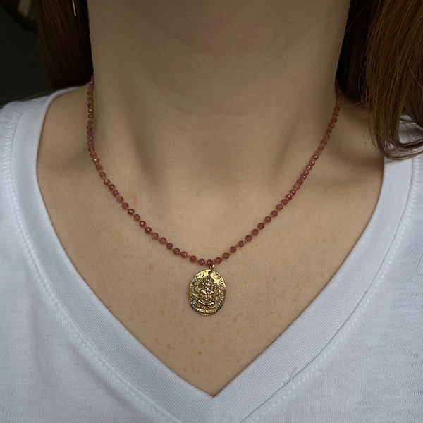 Bronze Ganesh Charm modeled on a lena skadegard pink tourmaline necklace on woman's neck