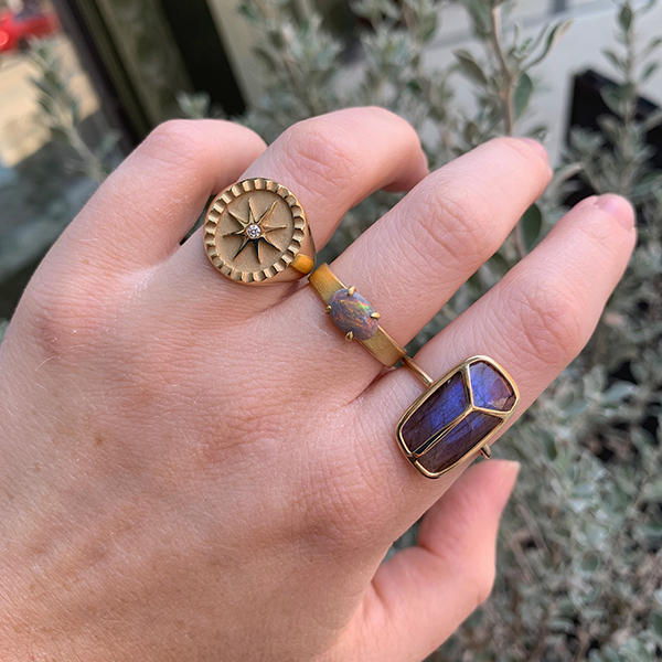 Pamela Zamore Star Signet modeled on a woman's hand with the Petite Baleine Australian Opal 18k Gold Wide Belt Ring and the Rachel Atherley 14k Gold Lucky Scarab Labradorite Ring