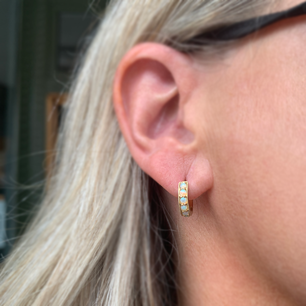 Gem Token 14k Gold Opal Huggie Earrings modeled on a woman's ear
