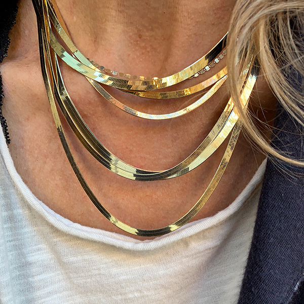 Gem Token Herringbone Chain Necklaces modeled on a woman's neck