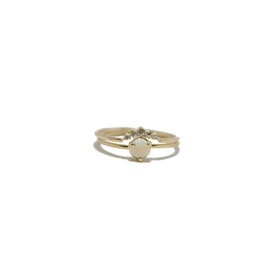 A simple 14k yellow gold band with a prong set round opal and a gold band with an arc of five diamonds stacked above it