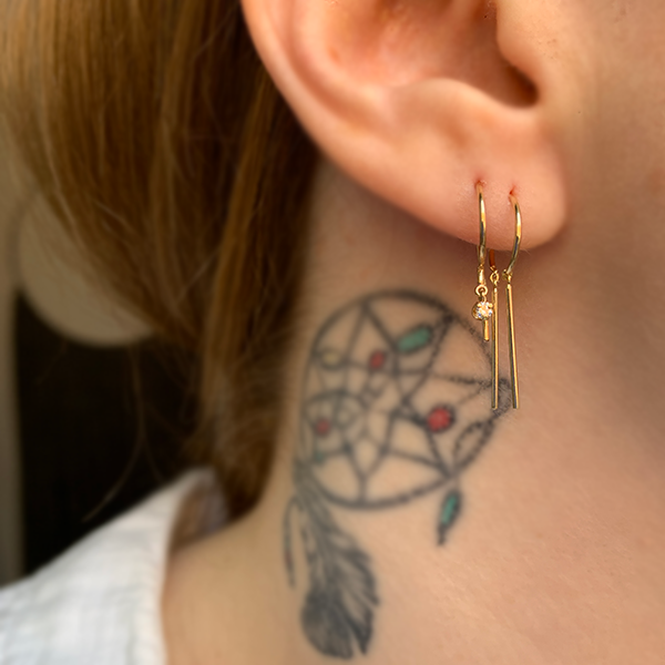 Jack & G Chime earrings and diamond loopdie earrings modeled on a woman's ear