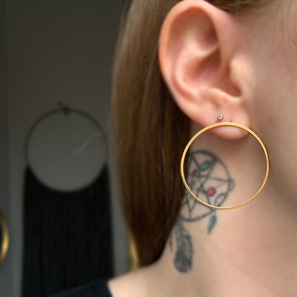 Tiny Anvil large Halo Stud Earrings modeled on a woman's ear