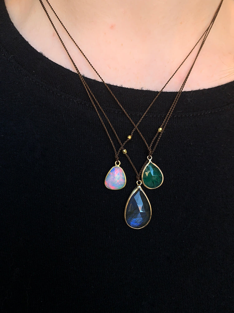 Margaret Solow 14k opal, labradorite, and emerald gemstone necklaces layered on a model's neck