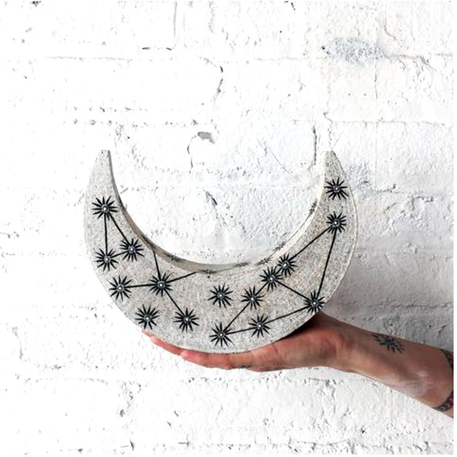 MQuan Crescent Moon Constellations Object held in front of a white brick wall