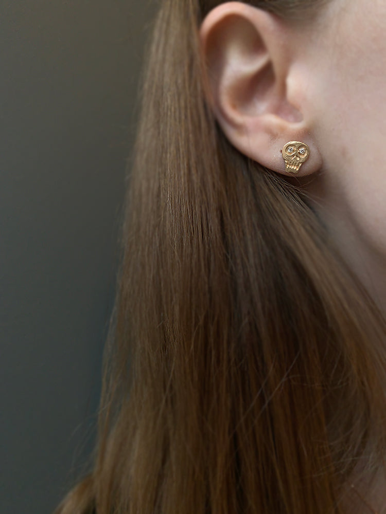 Petite Baleine 14k + Diamond Skull Earrings modeled on a woman's ear