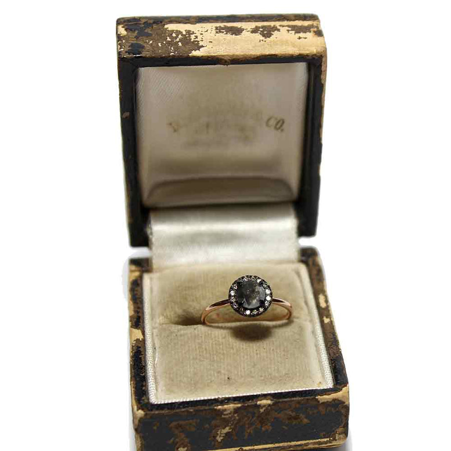 A rose cut black diamond with a rhodium plated white diamond halo on a 14k rose gold band