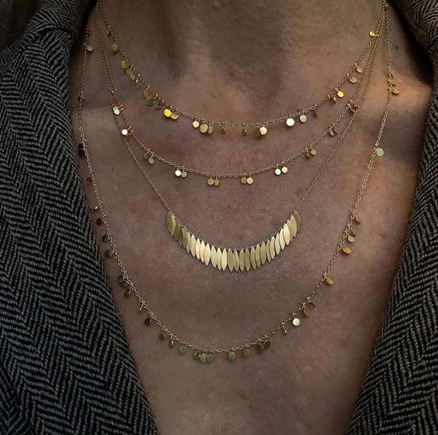 Sia Taylor 18k Gold necklaces layered on a woman's neck