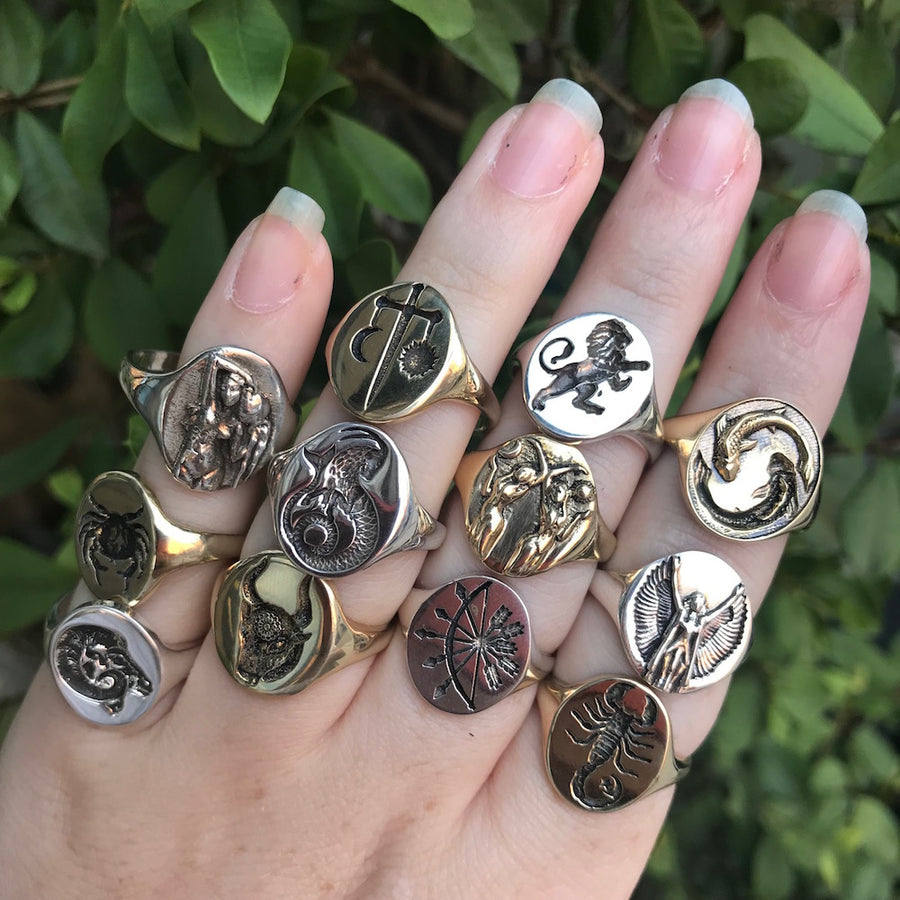 Talon bronze and silver zodiac signet rings modeled on a woman's hand