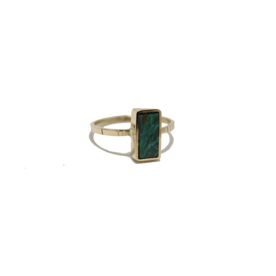 A rectangular piece of chrysocolla set in 14k gold on a gold band with carved detail
