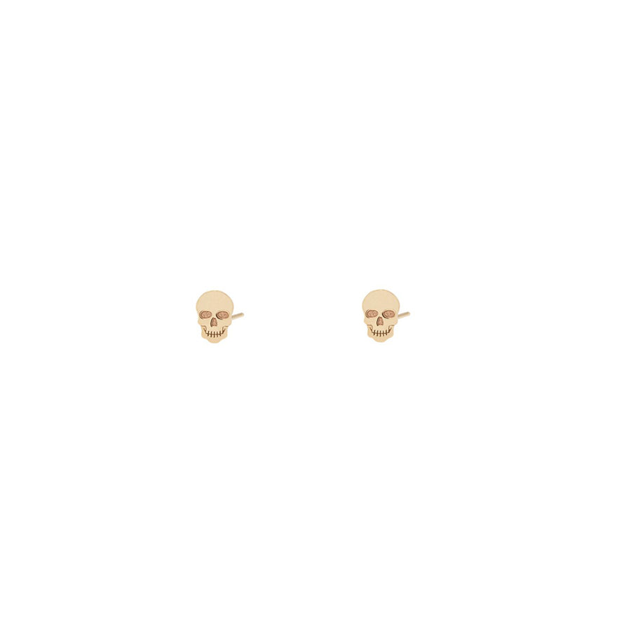 Tiny 14k yellow gold stud earrings in the shape of a skull