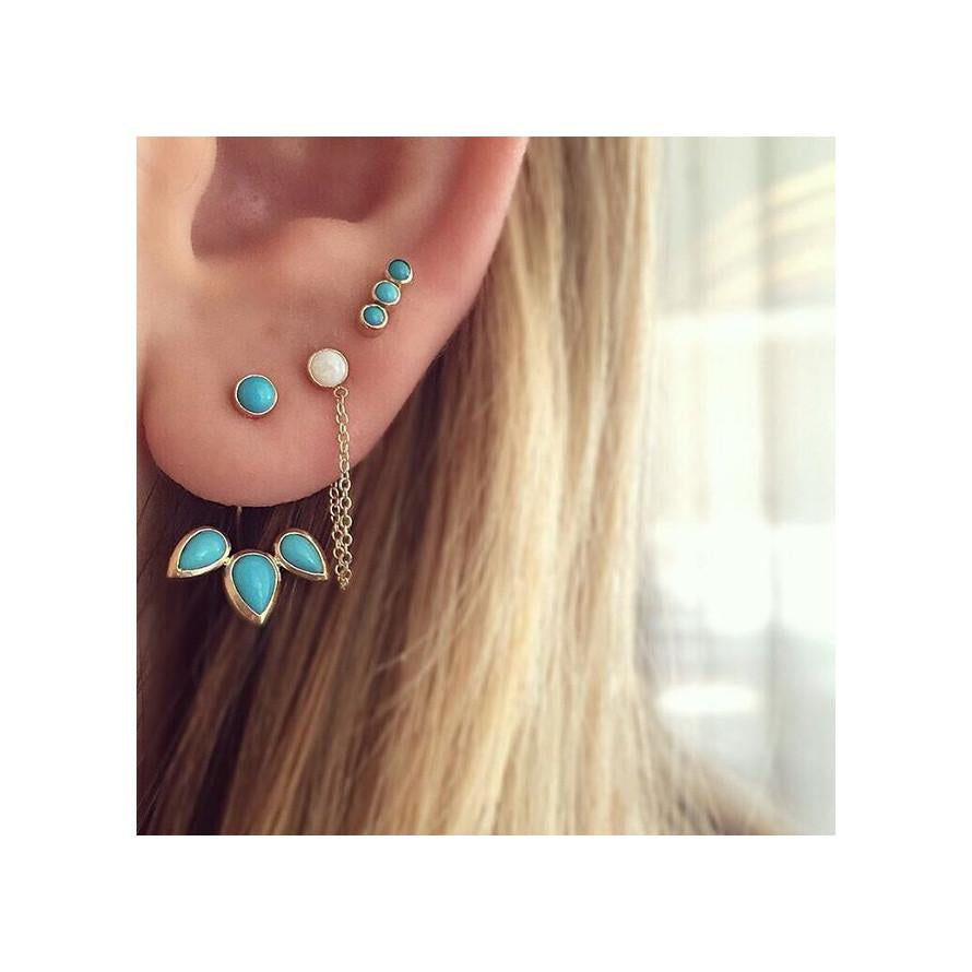 Zoe Chicco turquoise and opal gold stud earrings on a woman's ear