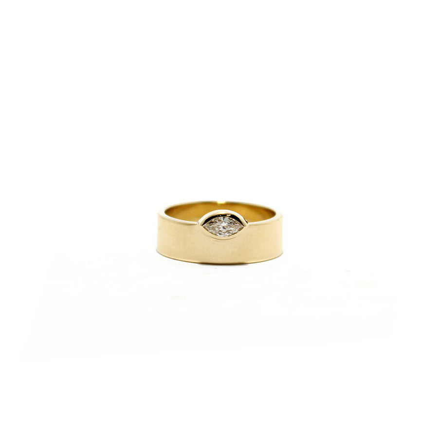 A 14k yellow gold wide flat band with an east-west set marquise diamond