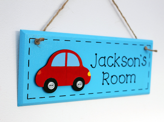 Blue wooden door sign with red car