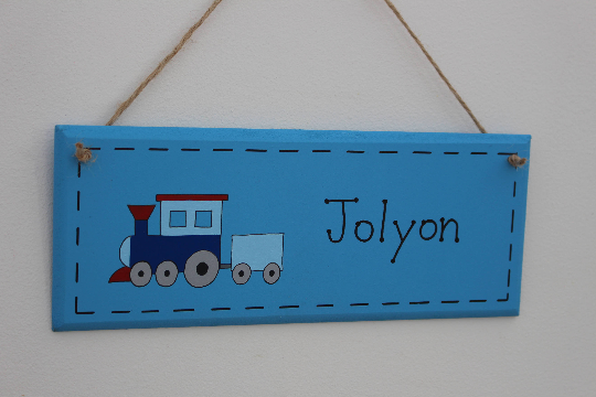 Blue wooden door sign with train illustration