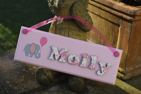 Pink wooden door sign with floral letters and elephant illustration