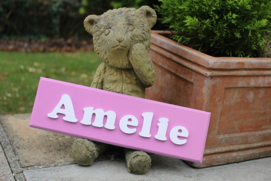 Pink wooden door sign with white wooden lettering