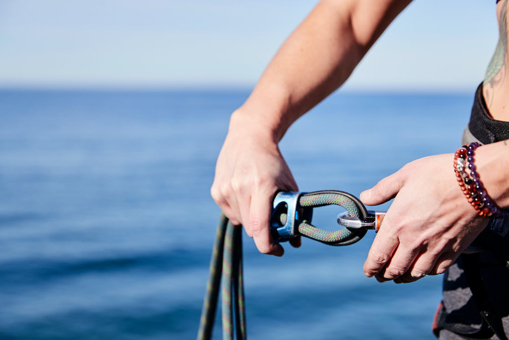 hands hitching rock climbing gear on ocean beackground