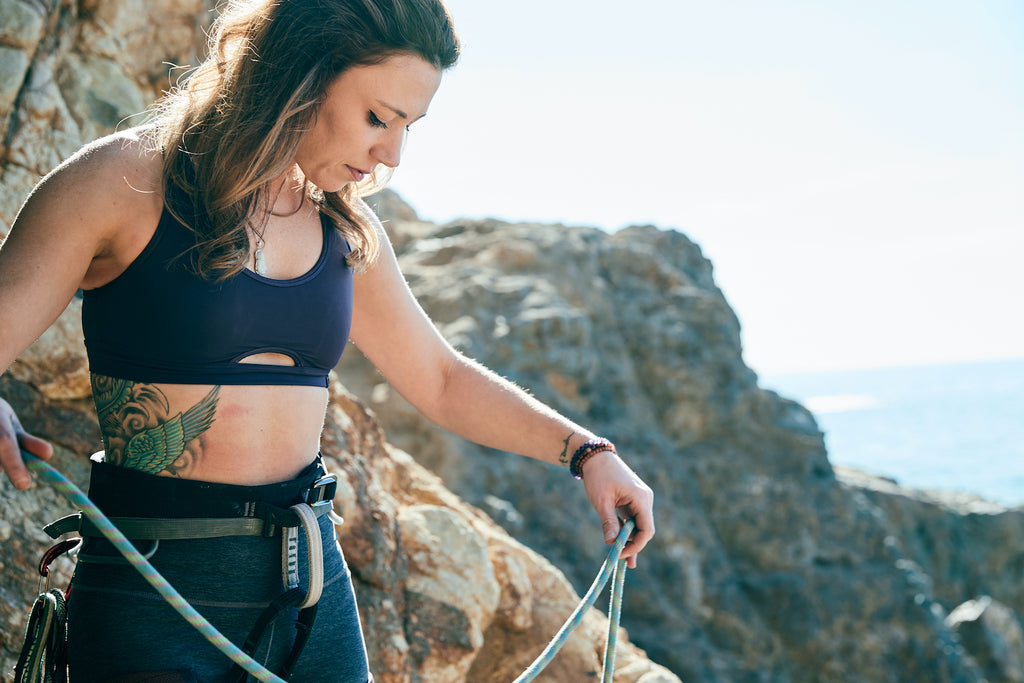 girl preparing rock climbing gear outside