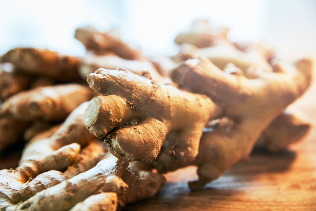 whole ginger root on a wooden chopping board