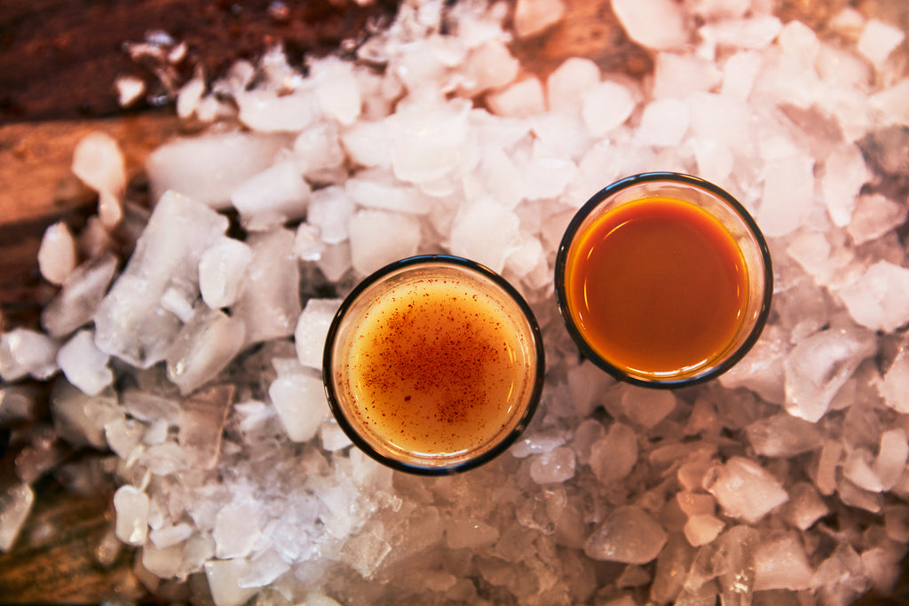 turmeric shots on ice on a wooden table