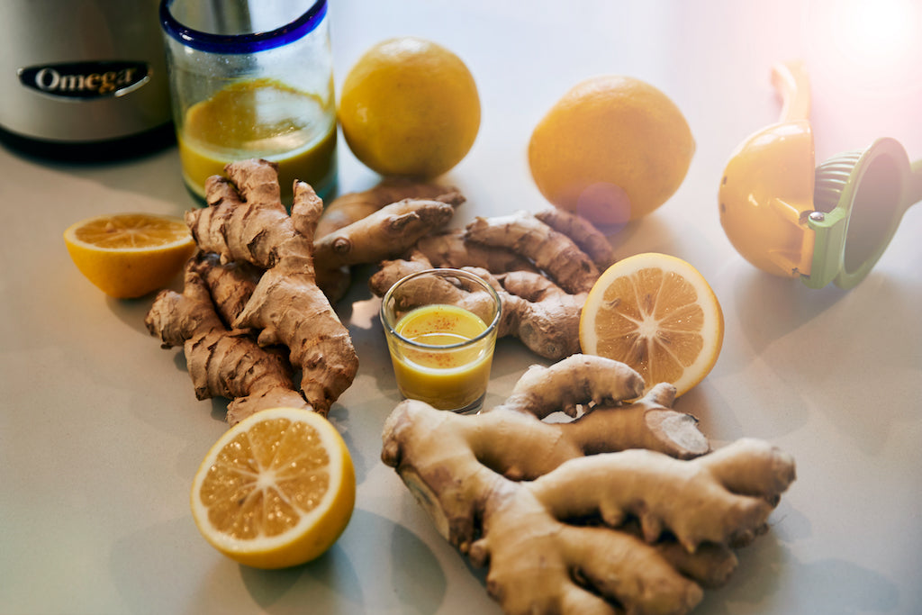 a white kitchen table with juicer and ingredients ginger lemon to make a shot