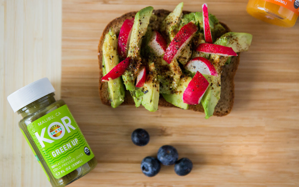 avocado toast on a wooden chopping board with green up