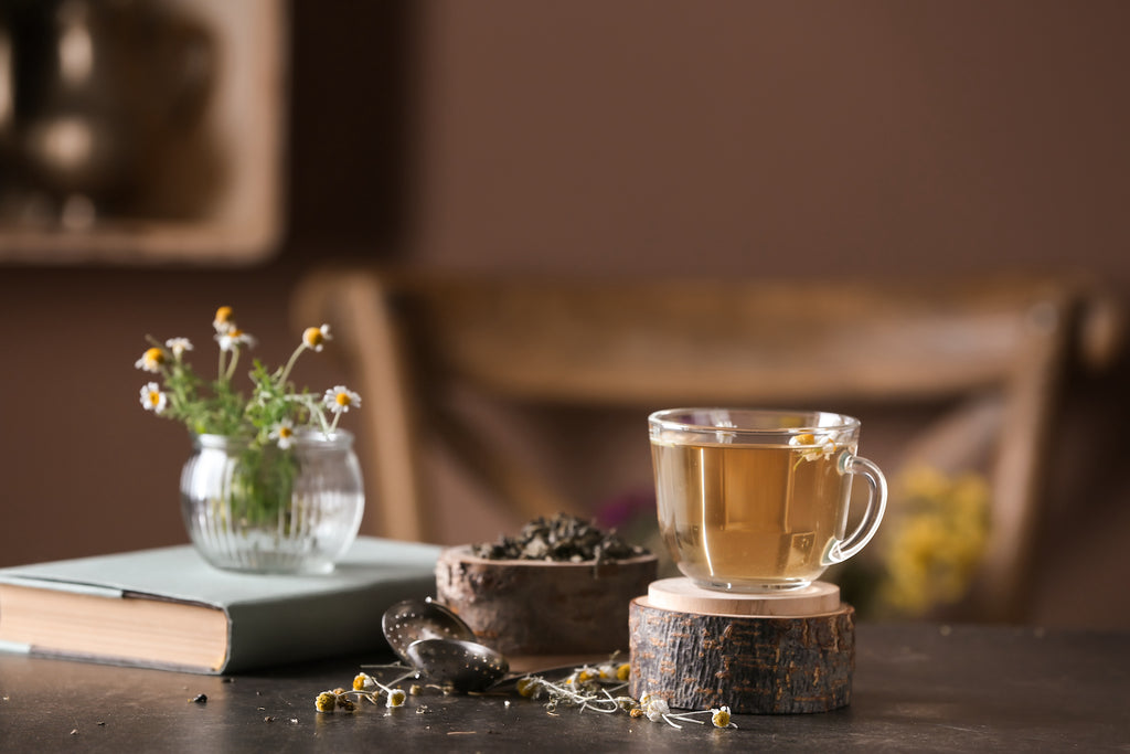 Glass mug of chamomile tea on wooden table