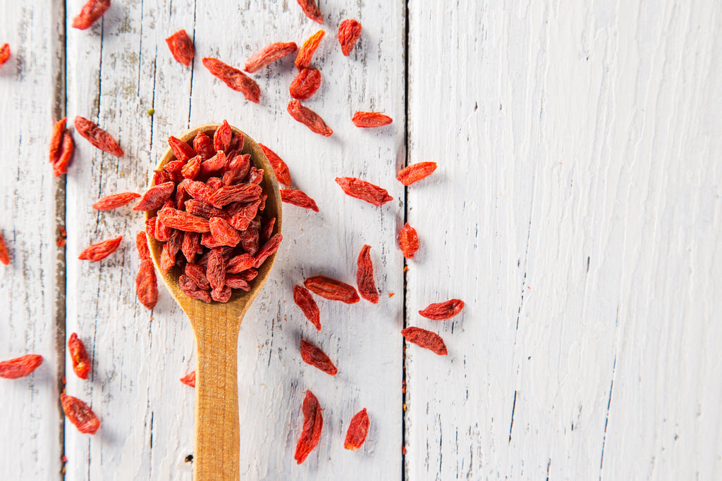 dry goji berry on wooden spoon on old white wooden background