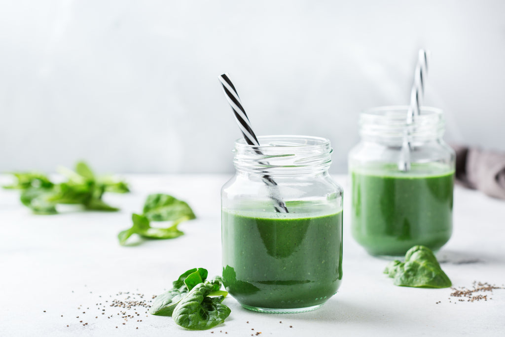 healthy green smoothie with spirulina on white background