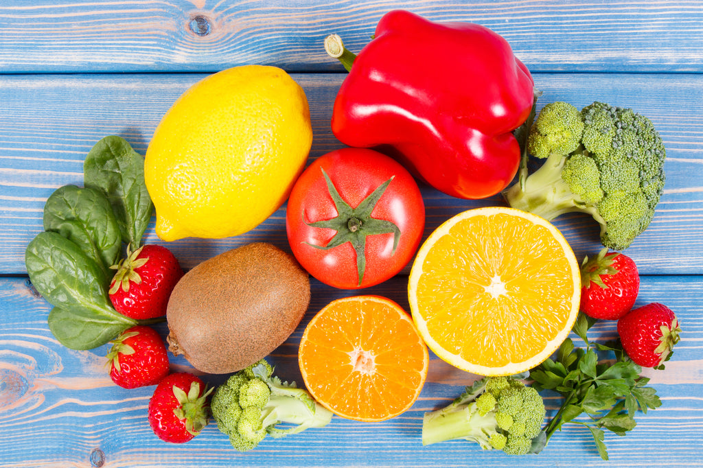foods rich in vitamin c red bell peppers, broccoli, lemons, oranges on wooden background