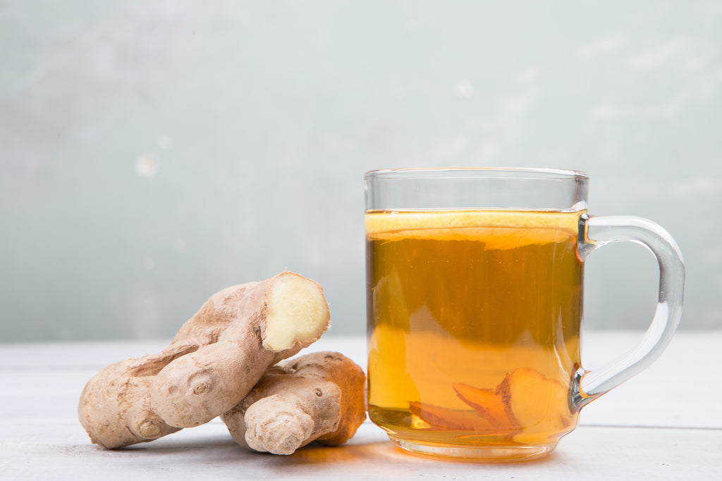 glass mug of ginger tea with ginger root on white background