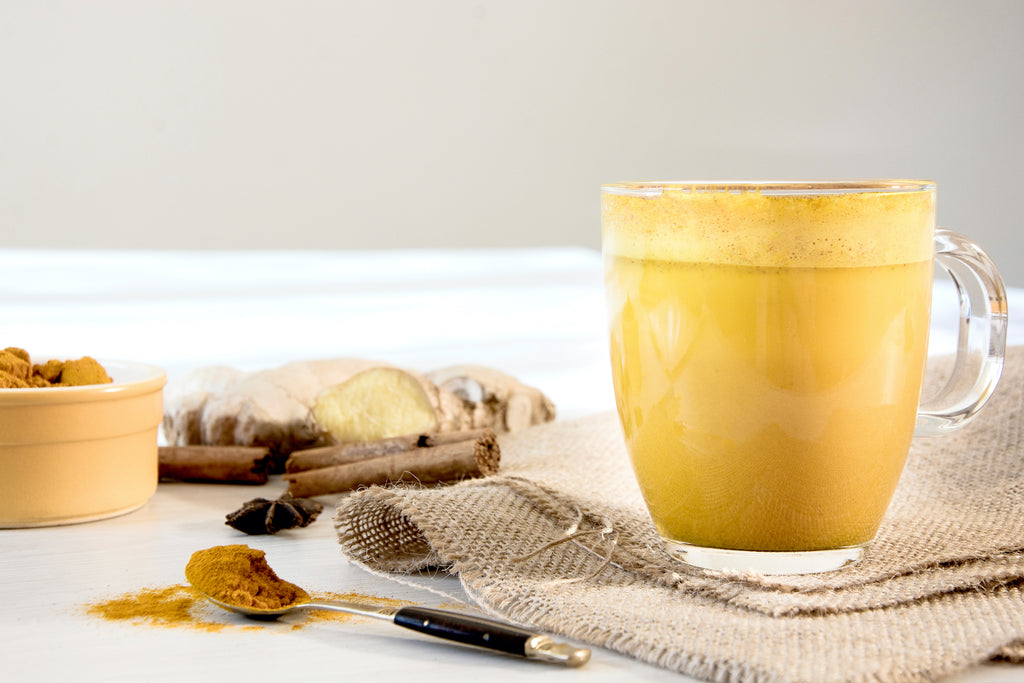 glass cup of golden milk with turmeric powder on a white table