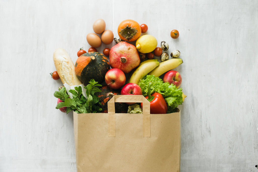 fresh produce in a paper bag on a white background