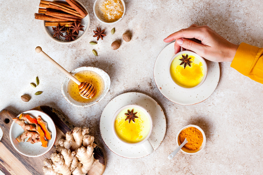 golden milk with ingredients on a white table