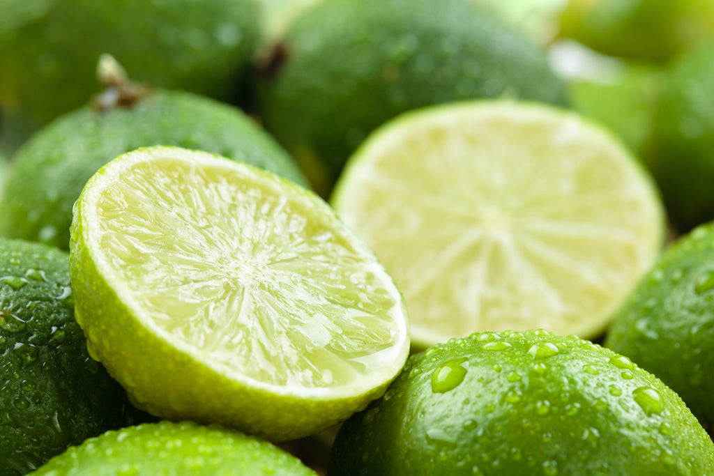 limes in a pile with one sliced in half