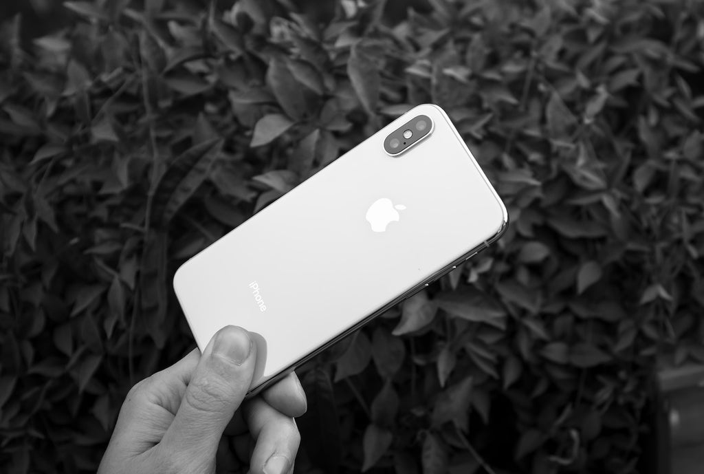 a hand holding an iphone in black and white