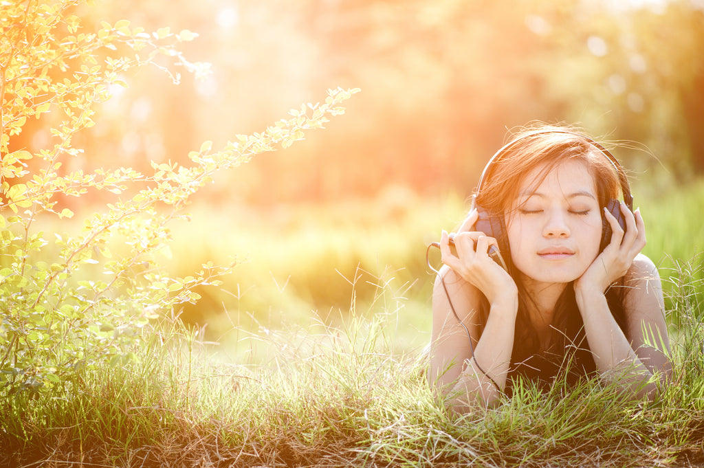 girl in a field listening to music