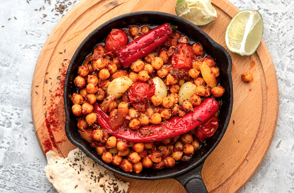 Spicy chickpeas with hot red peppers, tomatoes, cumin, garlic and other spices in a frying pan on a grey background top view