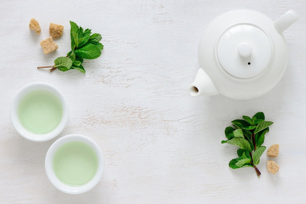 two cups of green tea and white teapot on wood