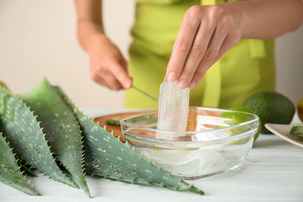 woman making aloe vera gel at a table