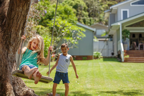 Children on Rope Swing Hanging from Tree Outside