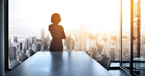 Female Executive Looks at City View from Panoramic Window